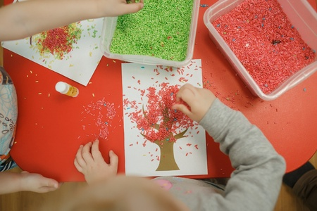 Group of children playing with colored rice from the sensory box. Painting exercise. Babys sensory educational kit