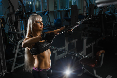 Muscular blonde woman doing pull ups training arms with trx fitness straps in the gym Concept workout healthy lifestyle sport. Girl in the gym exercises hand pulling the block.