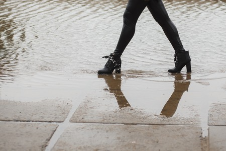 The girl in leather boots going on a big puddle in the city. Water Splashes from boots. Autumn or spring cold wet weather concept 版權商用圖片