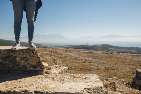Female tourist feet in ancient ruins. Panoramic view in mountains. Copy space. Tourism concept