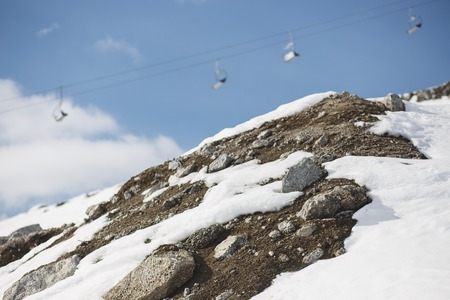 Rocks and snow with blurred ski-lift cable car and mountain range.