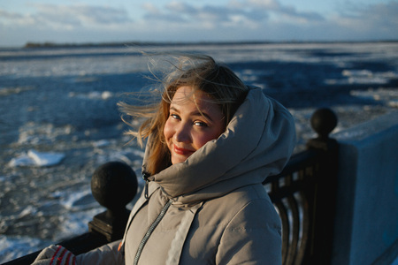 Portrait of pretty cheerful smiling woman on frozen river background in sunny winter day. Healthy winter walking in sinny frosty day Imagens