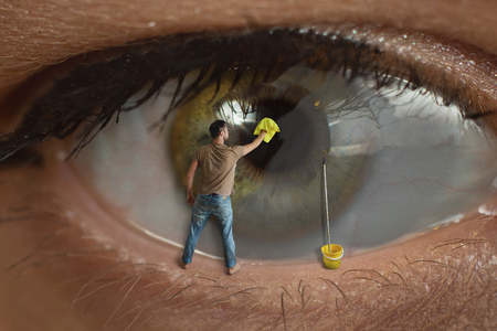 Male worker cleaning the surface of the pupil of the eye with a rag. Concept of healthy eyesight, conjunctivitis and window cleaning. 版權商用圖片