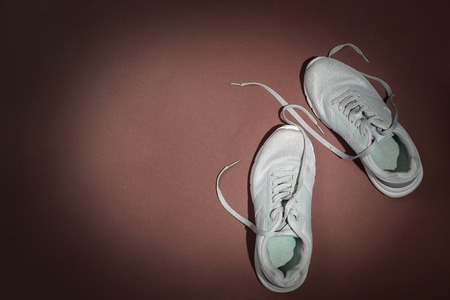 Trendy casual running shoes on brown background. Top view, minimalistic flat lay