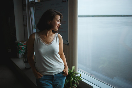 Young business woman in casual clothes looking to window in the office