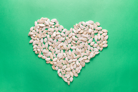 Heart shape of pumpkin seeds on green background. Minimalistic flat lay composition Stock Photo