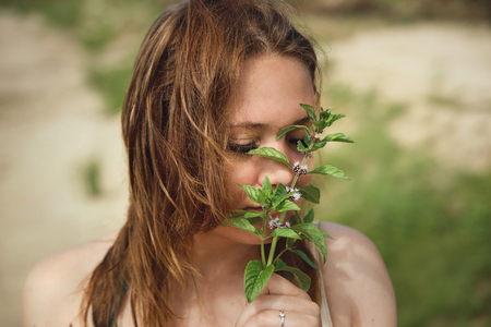 Beautiful woman smelling aroma of melissa grass in her hand.