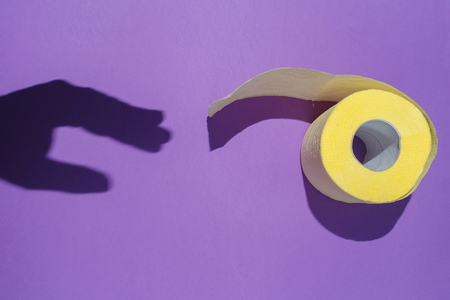 The hand shadow reaches for the yellow toilet paper on violet background. The concept of hygiene, issues of digestion. Flat lay, top view Banco de Imagens