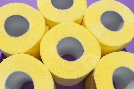 Pattern of bright yellow toilet paper rolls on purple background. Flat composition, top view