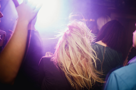 Anonymous girl having fun at party in night club, perfect long curly hair, back view