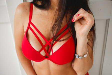 Close up of breast of woman presenting her bra. Red bra. Sexy boobs. Woman with big natural sexy boobs in lingerie. Closeup of sexy female boob in red bra. Plastic surgery. Sensual girl. Фото со стока