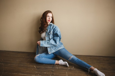 Sensual Female Model Posing in Denim Jacket, Jeans and White Socks on the Floor near Beige Wall. Back to 1990s Fashion Lifestyle Style Concept