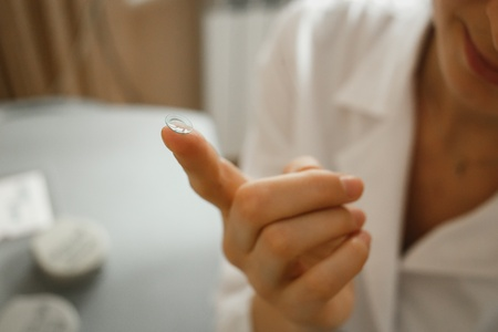 Female finger with contact lens on blurred background Imagens