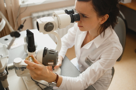 Attractive female doctor ophthalmologist is checking the eye vision of patient in modern clinic Stock Photo