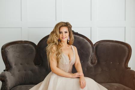 Beautiful blonde woman with greek hairstyle in beige powdery atlas wedding dress posing in studio room