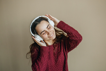 Enjoy the music. Happy young woman pleasing music in headphones.