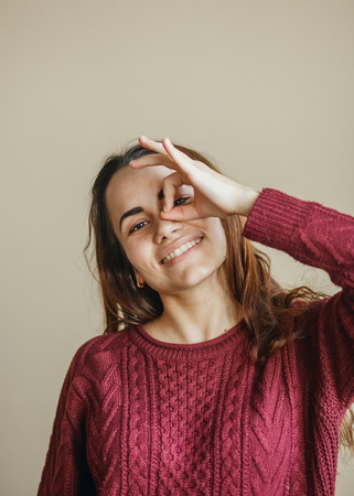 Happy young woman showing ok symbol and friendly looking to camera at beige wall. She clothed in burgundy sweater