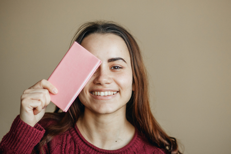 Happy young woman with pink diary friendly looking to camera at beige wall. She clothed in burgundy sweater
