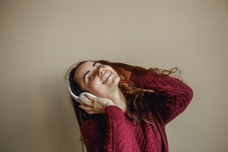 Enjoy the music. Happy young woman pleasing music in white headphones. She clothed in burgundy sweater