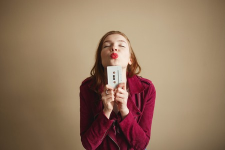 Young hipster woman with white retro audio cassette. Party 90s concept