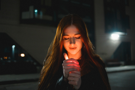 Young redhead woman with a burning lighter in the night city