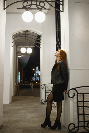 Mysterious redhead woman in elegant leather jacket coat and high heels walking in city street, noire atmosphere, intriguing concept