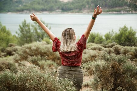 Girl on the top of mountain with hands up, green lake view behind Banco de Imagens