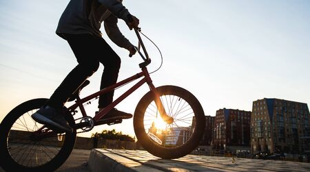 Bmx rider rides in the urban background of the sunset. Evening training at Bmx. Bmx Concept. Copyspace