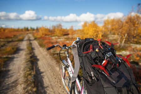 Bicycle with backpack and custom drone on the tundra road. Touring kit for travel blogger or photographer in autumn nature