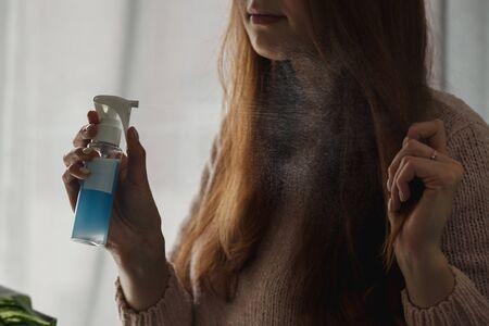Schöne Frau, die belebendes Haarspray auf Gesicht auf neutralem Haupthintergrund aufträgt.