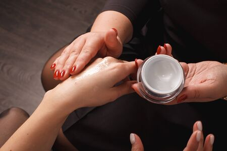 Women Hand With Cream. Closeup Beautiful Chubby Hands With Natural Manicure Nails Applying Cosmetic Moisturizing Hand Lotion On Soft Silky Skin. Beauty And Body Care Concept. Two person. Reklamní fotografie