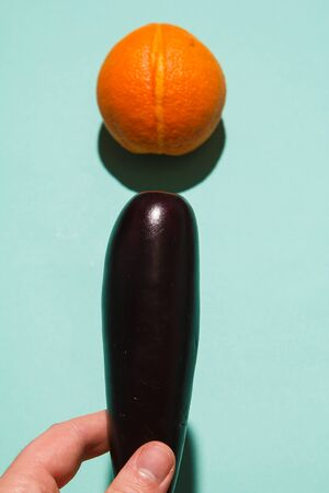 Interracial Sex concept - eggplant as penis and and a vulva-like orange