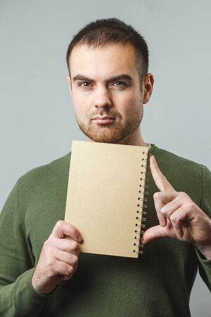 A young white man holds a notebook. Concept training, internship Vertical image