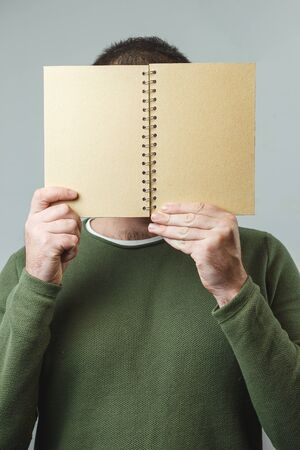 The man covers his face with a notebook. Vertical image