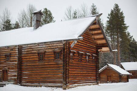 An old log cabin in a Russian village in winter.