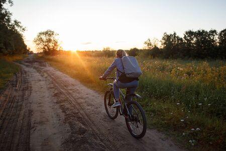 A woman rides her bike on a field road at sunset Reklamní fotografie