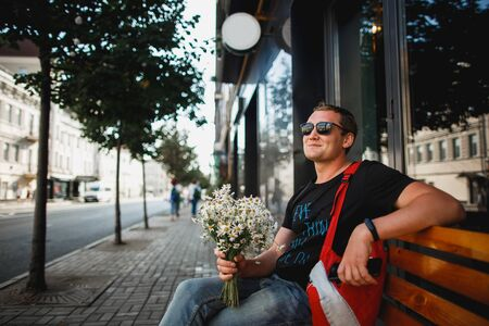 Joyful man sits on a bench with a bouquet of daisies waiting for a date Zdjęcie Seryjne