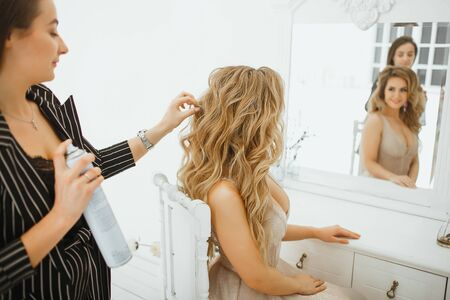 Stylist puts hairspray on a beautiful girl in an evening ball gown