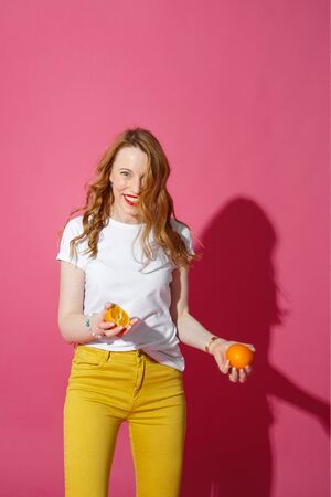 Orange fruits, healthy eating, true emotions - a young blonde woman juggling oranges on pink background