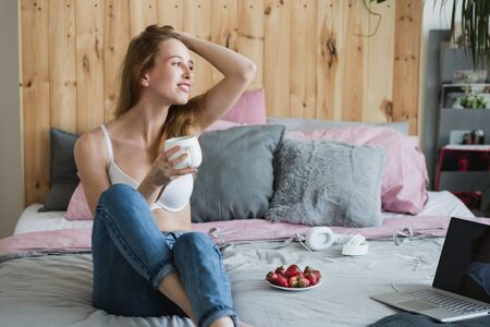 Blonde sexy woman with a cup of tea or coffee and strawberries having fun in bed. She wearing white bra and casual jeans. Happy morning
