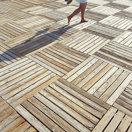 Vacation, travel, carefree concept. Female legs on wooden parquet on beach in sunny day. Square image