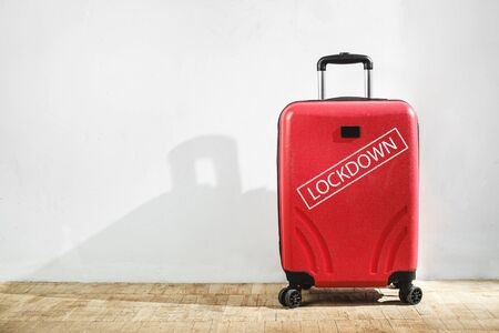 Red suitcase with lockdown inscription in the domestic room. Stay home no traveling concept. Copy space Zdjęcie Seryjne
