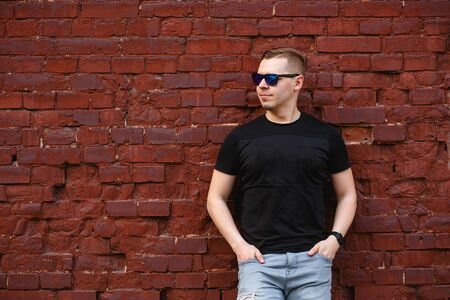Young man in a casual wear standing with his hands in his pockets by a brick wall