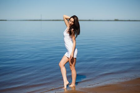 Young lady in the white dress standing in the warm water Imagens