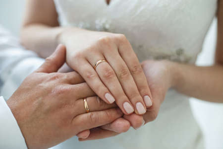 Bride putting a wedding ring on groom's finger. Pastel colors