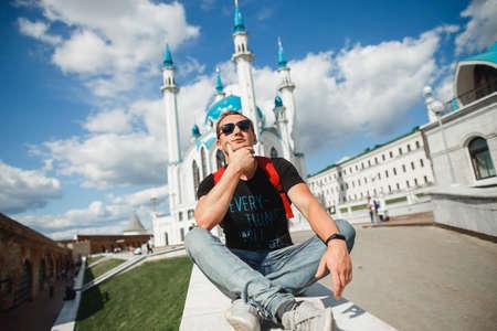 Handsome male tourist in glasses on the background Kul Sharif Mosque lis the main symbol of Kazan and touristic attraction. Kremlin, Kazan, Tatarstan, Russia
