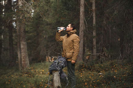 Hiker with backpack drinking water in deep forest
