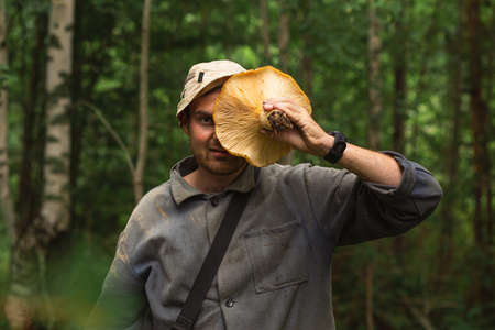 Man holding giant milk agaric in front of his face after picking them in forest on a autumn day