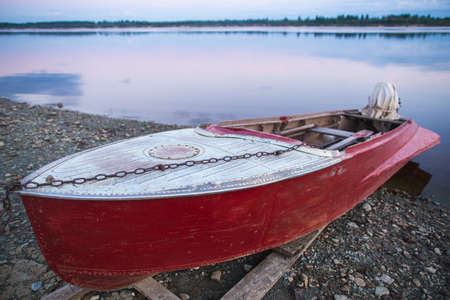 Old red rowboat lying at shore Banque d'images