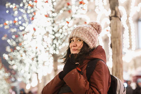 Outdoor night portrait of young fashionable woman in the winter hat with pompom. Happy in woman the Christmas street decorations. Night street illumination in Moscow